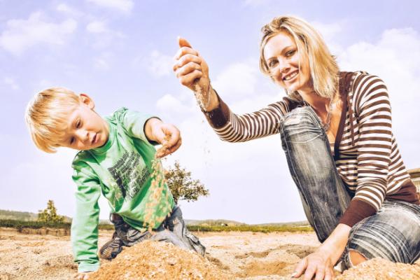 Babysitter mit Kind im Sand